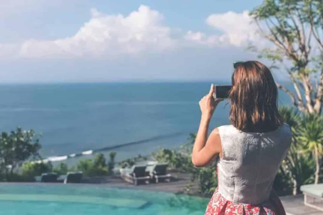 Jeune femme prenant en photo la mer
