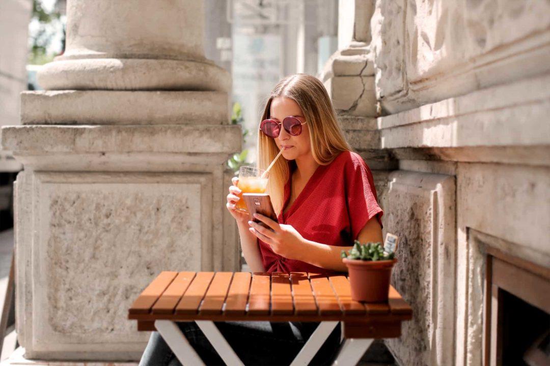 Jeune femme buvant sur un terrasse et utilisant son téléphone, carte sim albanie