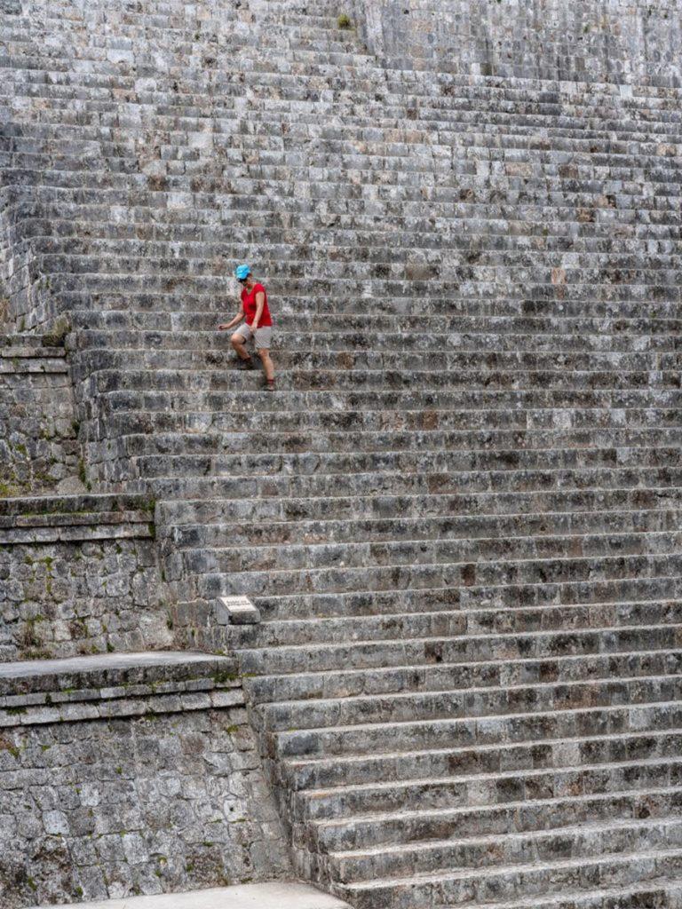 Homme montant les marches de la pyramide Kukulkán au Mexique, chichen itza curiosites