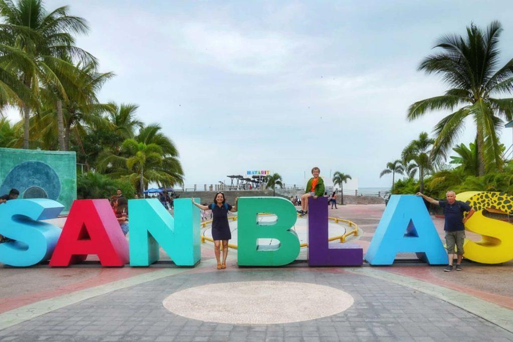 Jeune femme et enfant prenant une photo à côté des lettres colorées de San Blas, que faire riviera nayarit